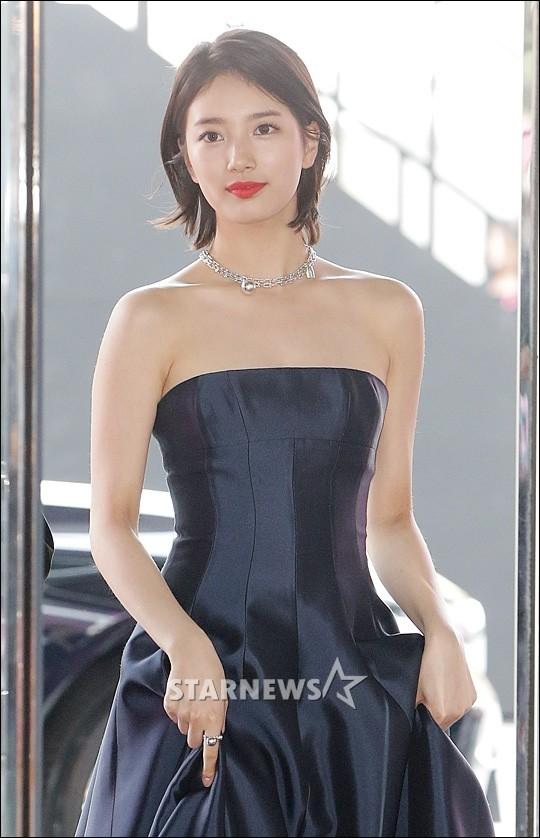 MC Suzy đơn giảntrong bộ trang phục xanh đen cùng điểm nhấn là một sợi dây chuyền ôm sát vòng cổ thanh mảnh.